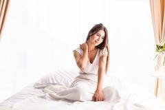 Frau, die mit einer Ausdehnung beim Sitzen im Bett aufwacht und gähnt stockbilder