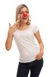 Frau, die mit einer roten Clownnase aufwirft Stockfoto