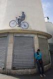 Frau, die mit einer Zeichnung von Hugo Chavez auf einem Fahrrad auf die Oberseite wartet Ca Stockfotografie