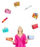 Frau, die mit einigen bunten Geschenken jongliert Lizenzfreie Stockbilder