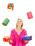 Frau, die mit einigen bunten Geschenken jongliert Stockbilder