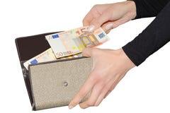 Frau, die mit Euro von ihrem Geldbeutel zahlt Stockbild