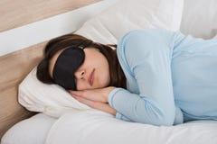 Frau, die mit Eyemask auf Bett schläft Stockbilder