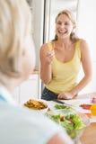 Frau, die mit Freund beim Vorbereiten der Mahlzeit spricht Stockfotos