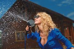 Frau, die mit Gartenschlauch wässert Stockfotografie