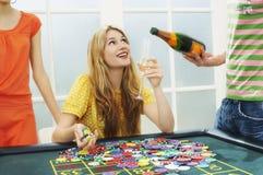 Frau, die mit geernteten Freunden am Roulettetisch feiert Lizenzfreie Stockfotos
