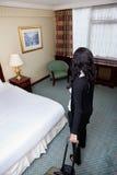 Frau, die mit Gepäck im Hotelzimmer steht Lizenzfreies Stockfoto