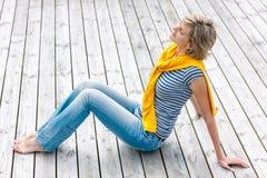 Frau, die mit geschlossenen Augen auf Bretterboden sitzt Lizenzfreies Stockbild