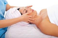 Frau, die mit Gesichtsmassage am Badekurort sich entspannt Stockfotografie