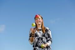 Frau, die mit gesunden Äpfeln jongliert Lizenzfreie Stockfotos