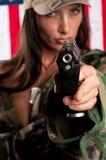 Frau, die mit Gewehr zeigt Lizenzfreie Stockbilder