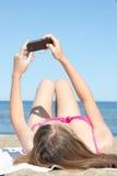 Frau, die mit Handy auf dem Strand sich fotografiert Stockbild