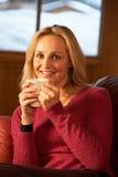 Frau, die mit heißem Getränk auf dem Sofa fernsieht sich entspannt Lizenzfreie Stockfotos
