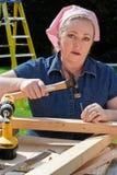 Frau, die mit Hilfsmitteln arbeitet Lizenzfreie Stockfotos
