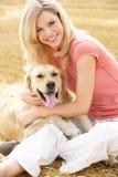 Frau, die mit Hund auf Stroh-Ballen sitzt, in geerntet lizenzfreie stockfotografie