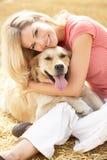 Frau, die mit Hund auf Stroh-Ballen sitzt, in geerntet stockfotos