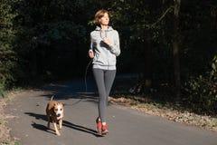 Frau, die mit Hund in einem Park rüttelt Junge weibliche Person mit Haustier d lizenzfreies stockfoto