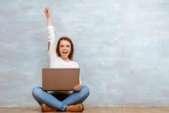 Frau, die mit ihr oben zeigen im Schneidersitz sitzt Lizenzfreies Stockfoto