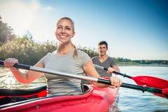 Frau, die mit ihrem Freund Kayak fährt lizenzfreie stockbilder