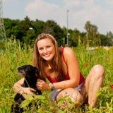 Frau, die mit ihrem Hund in einer Wiese spielt Lizenzfreie Stockfotos