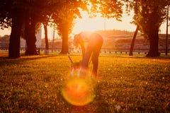 Frau, die mit ihrem Hund im Park bei Sonnenuntergang spielt Stockbild