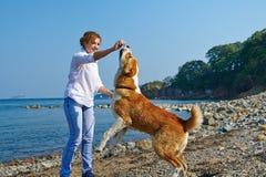 Frau, die mit ihrem Hund nahe Meer plaing ist Stockfotos