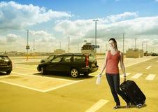 Frau, die mit ihrem Koffer am Autoparkplatz geht Stockbild