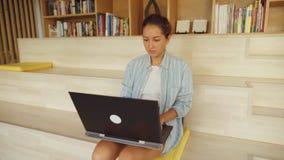 Frau, die mit ihrem Laptop stillsteht auf ihrem Schoss arbeitet stock video