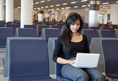 Frau, die mit ihrem Notizbuch im Flughafen arbeitet Lizenzfreie Stockfotos