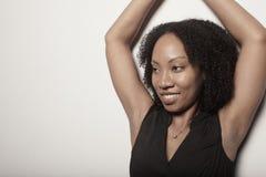 Frau, die mit ihren Armen über ihrem Kopf aufwirft Stockfotografie