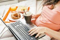 Frau, die mit ihrer Laptop-Computer arbeitet und frühstückt Stockbilder