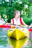 Frau, die mit Kanu auf Fluss schaufelt Lizenzfreie Stockfotografie
