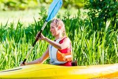 Frau, die mit Kanu auf Fluss schaufelt Stockfoto
