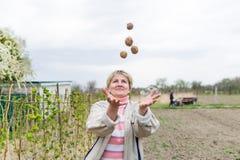 Frau, die mit Kartoffel jongliert Lizenzfreie Stockfotografie