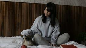 Frau, die mit Katze auf Bett sitzt stock footage