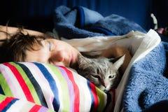 Frau, die mit Katze schläft Lizenzfreie Stockbilder