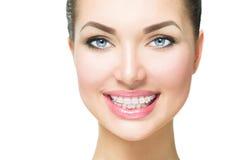 Frau, die mit keramischen Klammern auf Zähnen lächelt Stockfoto