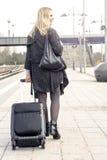 Frau, die mit Koffer an der Bahnstation geht Lizenzfreie Stockfotos