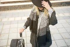 Frau, die mit Koffer an der Bahnstation wartet Lizenzfreie Stockfotografie