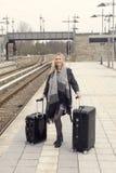 Frau, die mit Koffern an der Bahnstation steht Stockbilder
