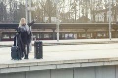 Frau, die mit Koffern an der Bahnstation steht Stockfotos