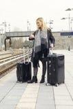 Frau, die mit Koffern an der Bahnstation wartet Lizenzfreie Stockfotografie