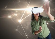 Frau, die mit Kopfhörer der virtuellen Realität mit hellem Verbindungshintergrund spielt Stockfotografie
