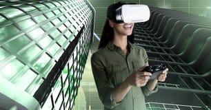 Frau, die mit Kopfhörer der virtuellen Realität und hohen Gebäuden mit Gitterhintergrund spielt Lizenzfreies Stockfoto