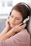 Frau, die mit Kopfhörer träumt Stockbild