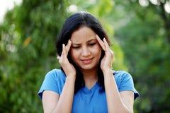 Frau, die mit Kopfschmerzen leidet Stockbild
