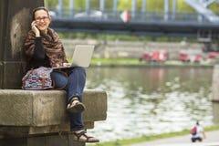 Frau, die mit Laptop auf der Ufergegend der alten Stadt sitzt und am Telefon spricht freiberufler Stockbild
