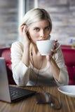 Frau, die mit Laptop-Computer im Café arbeitet Lizenzfreie Stockbilder