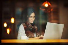 Frau, die mit Laptop im Café arbeitet lizenzfreie stockbilder