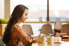 Frau, die mit Laptop im Café arbeitet lizenzfreies stockfoto